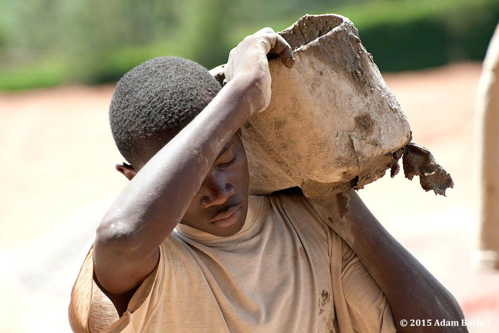 portland oregon editorial photographer in rwanda -man carrying bucket of cement