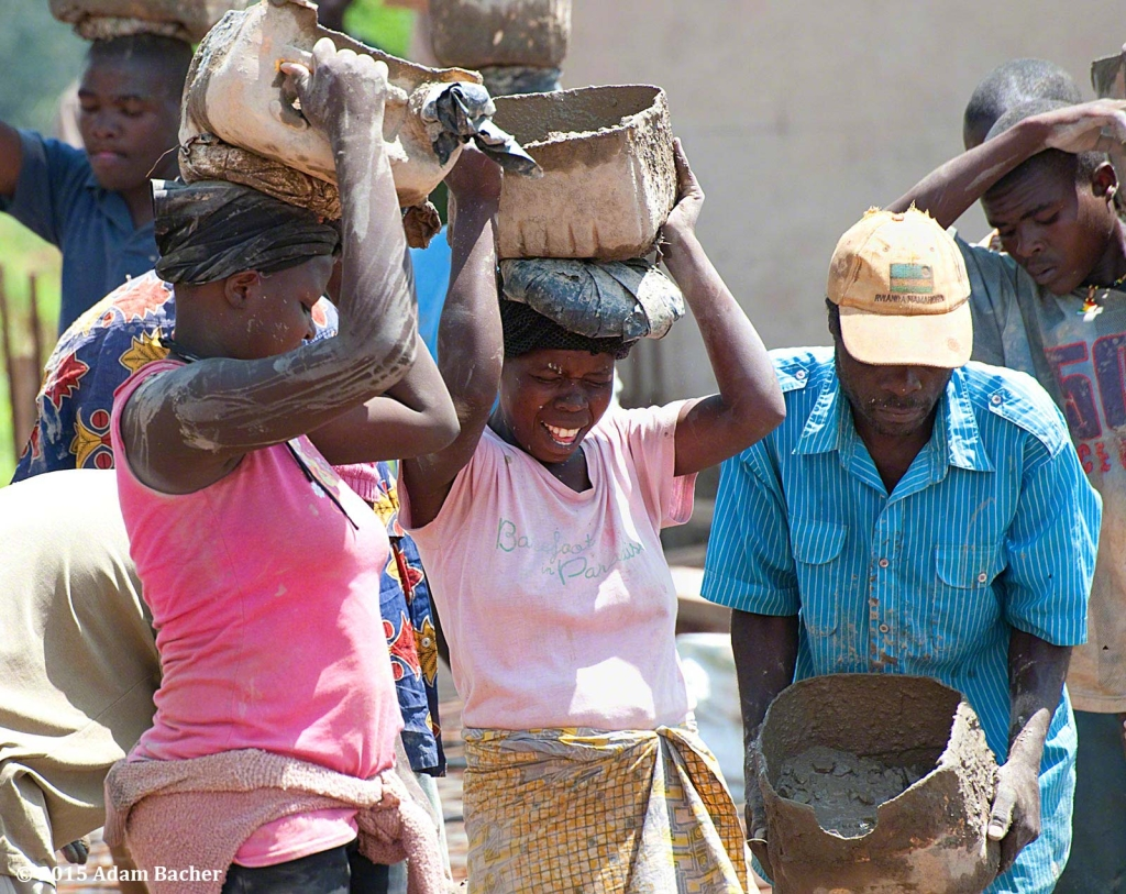 editorial photographer from portland oregon  in rwanda - woman carrying  cement